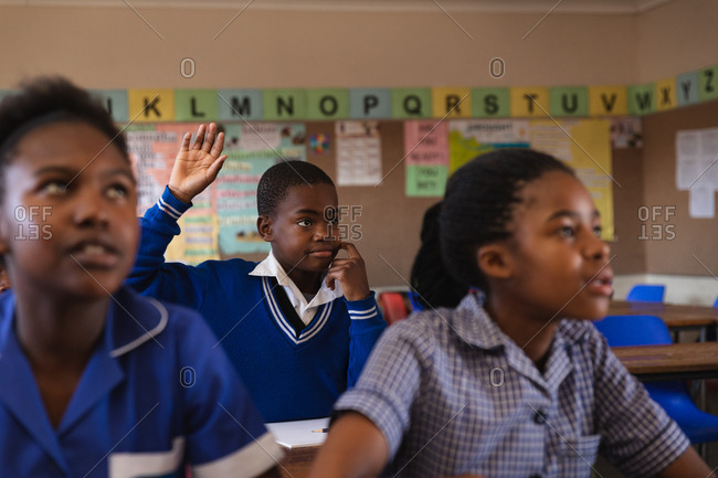 Front view of a young African schoolboy sitting at his desk, raising his hand to answer a question during a lesson in a township elementary school classroom, in the foreground two schoolgirls are listening attentively