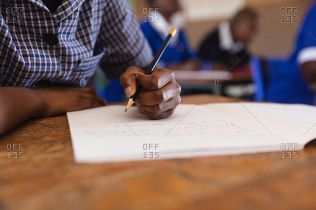 Front view mid section of a young African schoolgirl sitting at her desk and writing with a pencil in her notebook during a lesson in a township elementary school classroom, in the background her classmates are also writing in their books