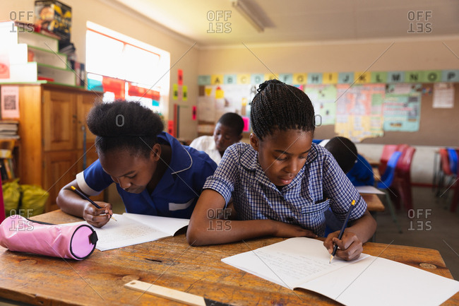 Front view close up of a two young African schoolgirls writing in their notebooks during a lesson in a township elementary school classroom, in the background their classmates are also writing in their books