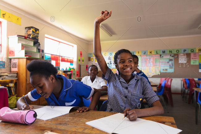 Front view of two young African schoolgirls sitting at their desk, one raising her hand to answer a question and the other writing in her notebook during a lesson in a township elementary school classroom, in the background their classmates are listening attentively