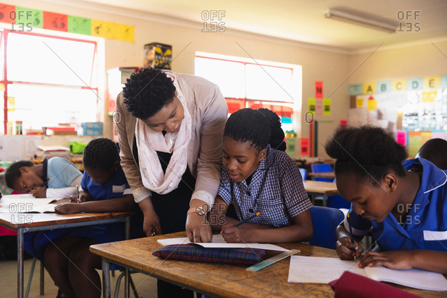 Middle aged African female school teacher helping a young schoolgirl sitting at her desk during a lesson in a township elementary school classroom in Cape Town, South Africa