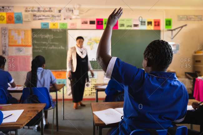Rear view of a young African schoolgirl raising her hand to answer a question to the female teacher standing at the front of the class during a lesson in a township elementary school classroom