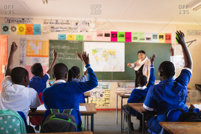 Rear view of a young African schoolchildren raising their hands to answer a question to the female teacher standing at the front of the class by the blackboard during a lesson in a township elementary school classroom