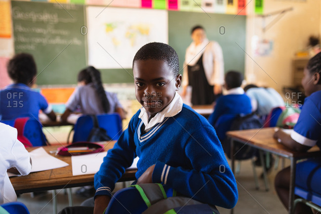 Side view close up of a young African schoolboy sitting at his desk and turning around, looking to camera and smiling during a lesson in a township elementary school classroom. In the background the rear view of his classmates listening to the teacher standing at the front of the class by the blackboard