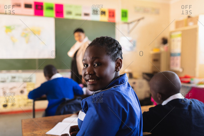 Side view close up of a young African schoolgirl sitting at her desk and turning around, looking to camera and smiling during a lesson in a township elementary school classroom. In the background the rear view of her classmates listening to the teacher standing at the front of the class by the blackboard