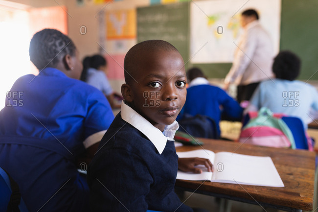 Side view close up of a young African schoolboy sitting at his desk and turning around, looking to camera during a lesson in a township elementary school classroom. In the background the rear view of his classmates listening to the teacher standing at the front of the class by the blackboard