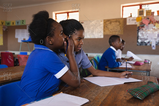 Side view close up of two young young African schoolgirls sitting at their desk whispering to each other during a lesson in a township elementary school classroom. In the background their classmates are listening to the teacher