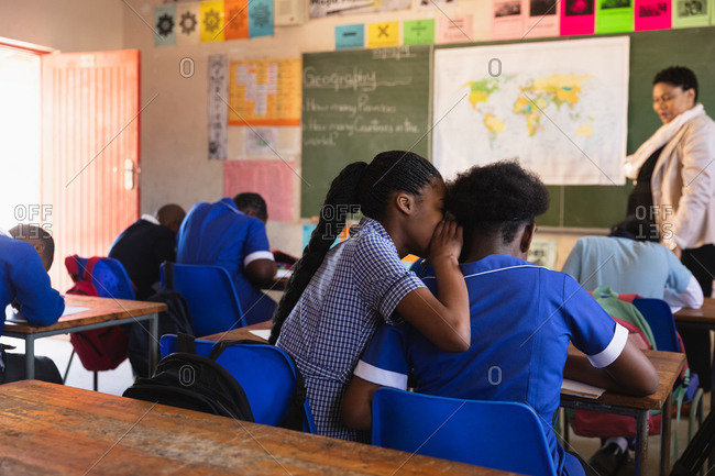 Rear view of two young African schoolgirls sitting at their desk whispering to each other during a lesson in a township elementary school classroom. In the background the rear view of their classmates listening to the teacher standing at the front of the class by the blackboard