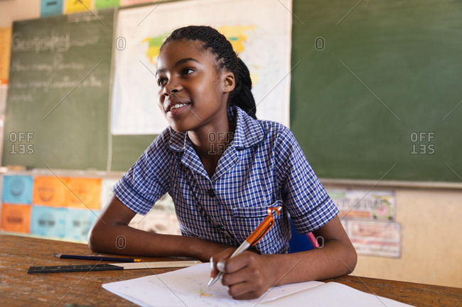 Front view close up of a young African schoolgirl sitting at a desk smiling, writing in her note book and listening attentively during a lesson in a township elementary school classroom