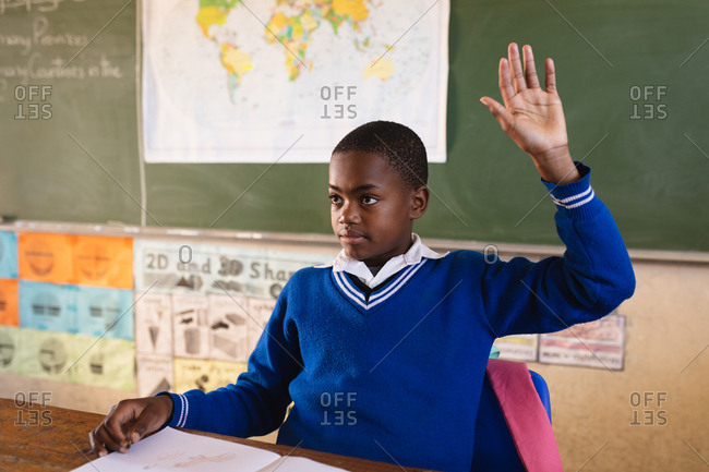 Front view close up of a young African schoolboy sitting at a desk and raising his hand to answer a question during a lesson in a township elementary school classroom, in the background is a world map and the blackboard