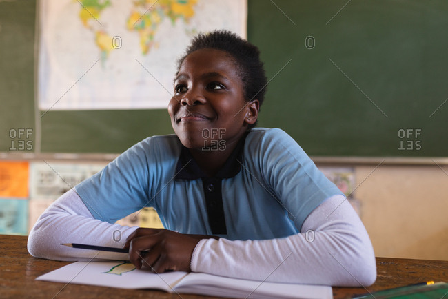 Front view close up of a young African schoolgirl sitting at a desk smiling and listening attentively during a lesson in a township elementary school classroom