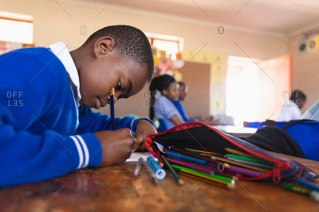 Side view close up of a young African schoolboy sitting at his desk writing during a lesson in a township elementary school classroom, in the background classmates are aldo sitting at their desks writing