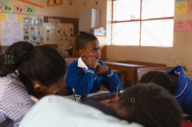 Side view of a young African schoolboy sitting at his desk, leaning and listening during a lesson in a township elementary school classroom, around him classmates are sitting at their desks writing