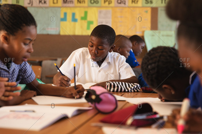 Front view of a young African schoolboy sitting at his desk writing during a lesson in a township elementary school classroom, around him classmates are also sitting at their desks writing