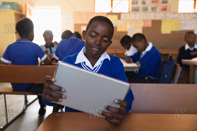 Front view close up of a young African schoolboy sitting at his desk looking at a tablet computer and smiling during a lesson in a township elementary school classroom,  in the background classmates are sitting at their desks working