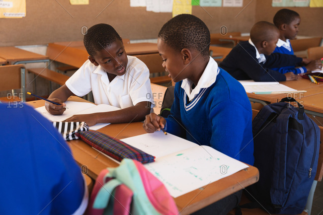 Front view close up of two young African schoolboys sitting at a desk writing and talking during a lesson in a township elementary school classroom, in the background classmates are also sitting at desks writing