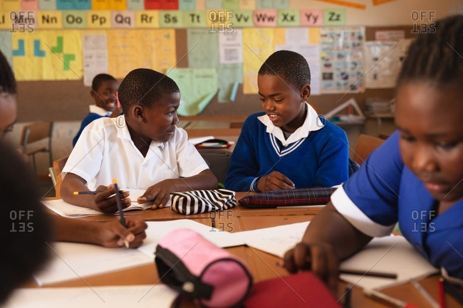 Front view of two young African schoolboys sitting at a desk writing and talking during a lesson in a township elementary school classroom, around them classmates are also sitting at desks writing