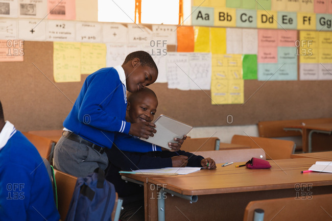 Front view of two young African schoolboys looking at a tablet computer and talking during a lesson in a township elementary school classroom. One boy is standing holding the tablet and showing it to the other boy who is sitting at a desk writing