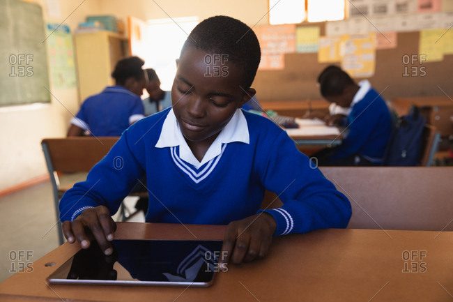 Front view close up of a young African schoolboy sitting at his desk using a tablet computer and smiling during a lesson in a township elementary school classroom, in the background classmates are sitting at their desks working