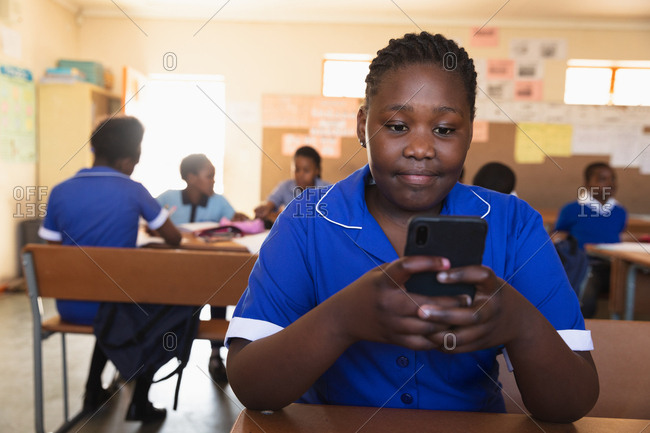 Front view close up of a young African schoolgirl sitting at her desk using a smartphone and smiling in a classroom at a township elementary school. In the background classmates are sitting at their desks working