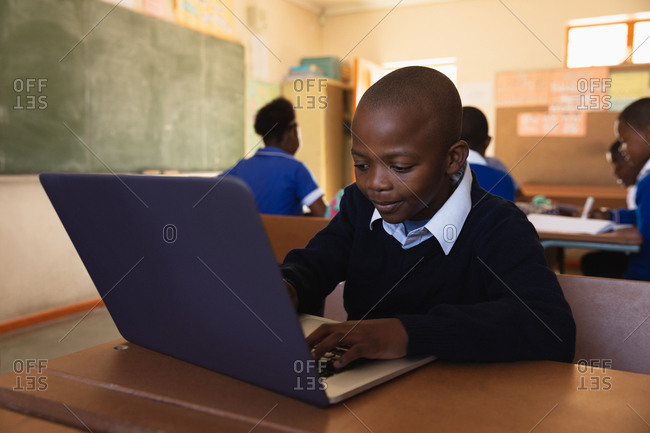 Front view close up of a young African schoolboy sitting at his desk using a laptop computer and smiling during a lesson in a township elementary school classroom, in the background classmates are sitting at their desks working