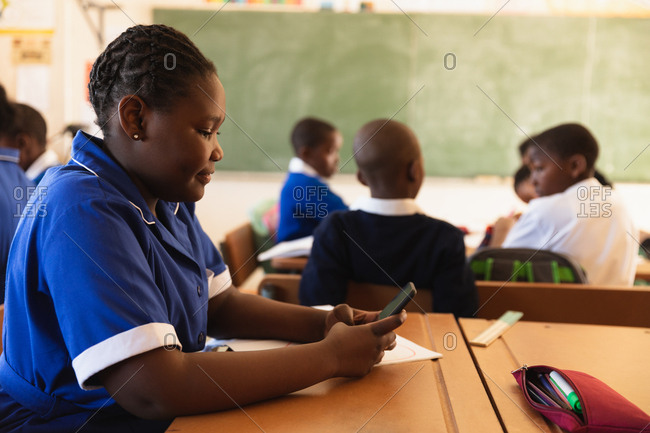 Side view close up of a young African schoolgirl sitting at her desk using a smartphone and smiling in a classroom at a township elementary school. In the background classmates are sitting at their desks working