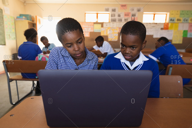 Front view close up of a young African schoolboy and schoolgirl sitting at a desk using a laptop computer together during a lesson in a township elementary school classroom, in the background classmates are sitting at their desks working