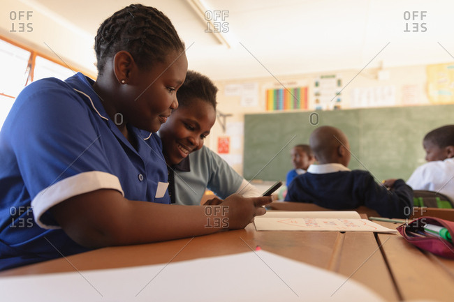 Side view close up of two young African schoolgirls sitting at a desk using a smartphone together and smiling in a classroom at a township elementary school. In the background classmates are sitting at their desks working