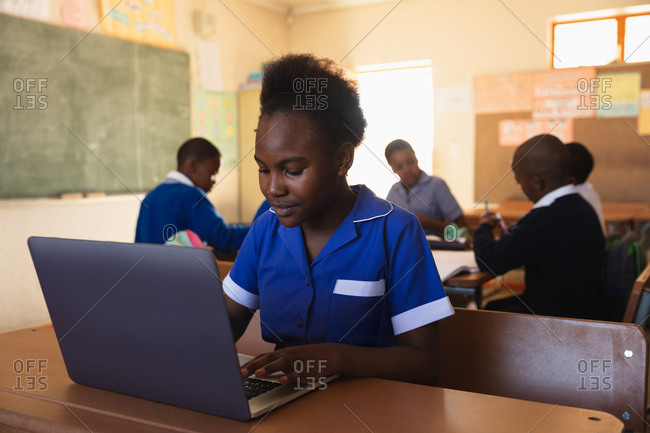 Front view close up of a young African schoolgirl sitting at a desk using a laptop computer and smiling during a lesson in a township elementary school classroom, in the background classmates are sitting at their desks working