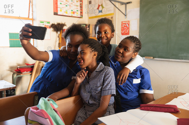 Front view close up of a group of young African schoolgirls having fun posing and taking selfies with a smartphone during a break from lessons in a township elementary school classroom