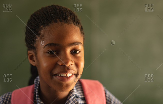Portrait close up of a young African schoolgirl wearing her school uniform and schoolbag, looking straight to camera smiling, at a township elementary school