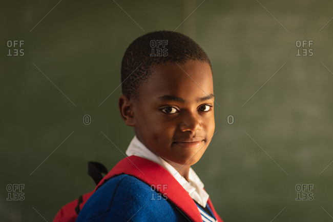 Portrait close up of a young African schoolboy wearing his school uniform and schoolbag, looking straight to camera smiling, at a township elementary school