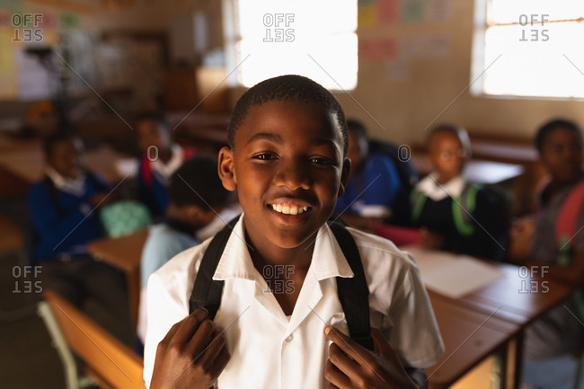 Portrait close up of a young African schoolboy wearing his school uniform and schoolbag, looking straight to camera smiling, at a township elementary school with classmates sitting at desks in the background