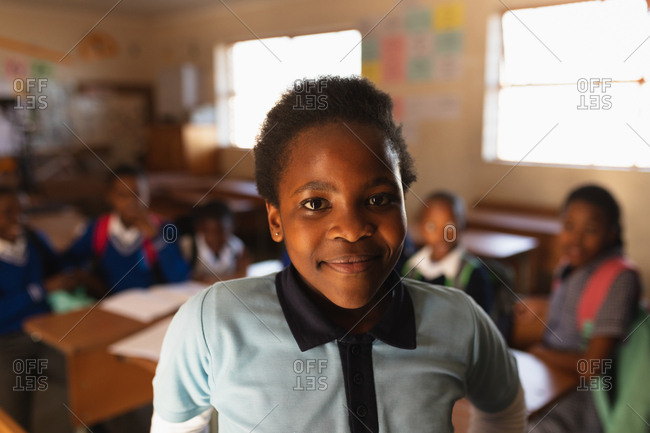 Portrait close up of a young African schoolgirl wearing her school uniform and schoolbag, looking straight to camera smiling, at a township elementary school with classmates sitting at desks in the background