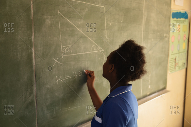 Side view close up of a young African schoolgirl standing at the front of the class writing on the blackboard during a lesson in a township elementary school classroom