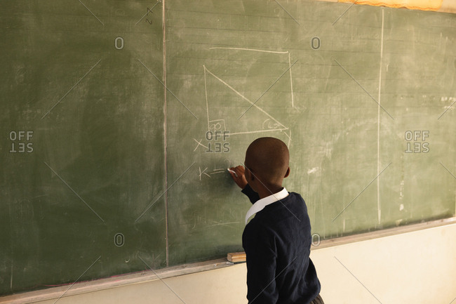 Back view of a young African schoolboy standing at the front of the class writing on the blackboard during a lesson in a township elementary school classroom