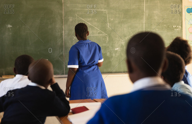 Back view of a young African schoolgirl standing at the front of the class writing on the blackboard during a lesson in a township elementary school classroom in Cape Town, South Africa