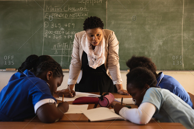 African female school teacher standing at the blackboard and leaning forward to watch her pupils writing at their desks in a township elementary school classroom, Cape Town, South Africa