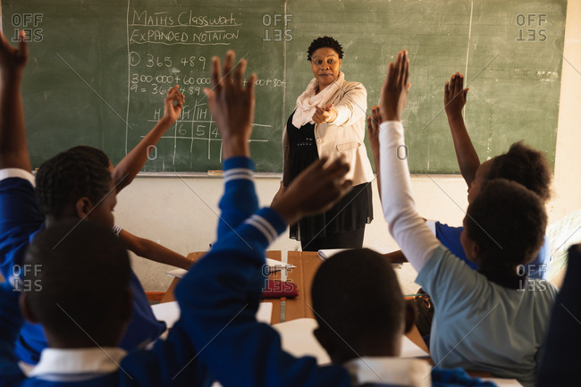 Front view of a middle aged African female school teacher standing at the front of the class in front of the blackboard with the rear view of pupils sitting at their desks with hands raised in the foreground during a lesson in a township elementary school classroom