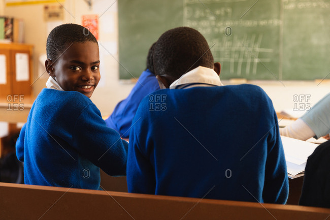 Side view close up of a young African schoolboy sitting at his desk and turning around, looking to camera and smiling during a lesson in a township elementary school classroom. Beside him and in the background the rear view of his classmates working