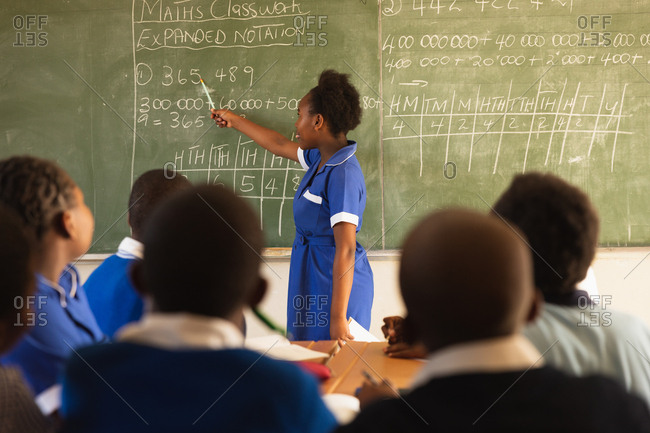 Side view of a young African schoolgirl standing at the front of the class writing on the blackboard during a lesson in a township elementary school classroom. In the foreground the back view of her classmates watching
