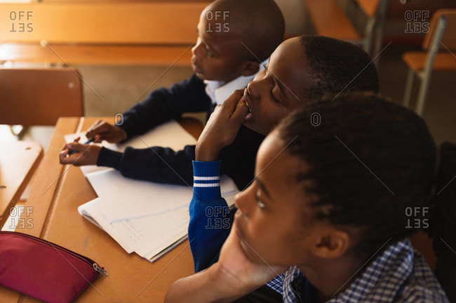Elevated side view close up of a young African schoolgirl and two schoolboys sitting at a desks listening during a lesson in a township elementary school classroom