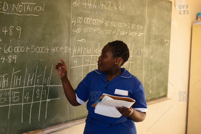 Front view close up of a young African schoolgirl standing at the front of the class holding a book and writing on the blackboard during a lesson in a township elementary school classroom