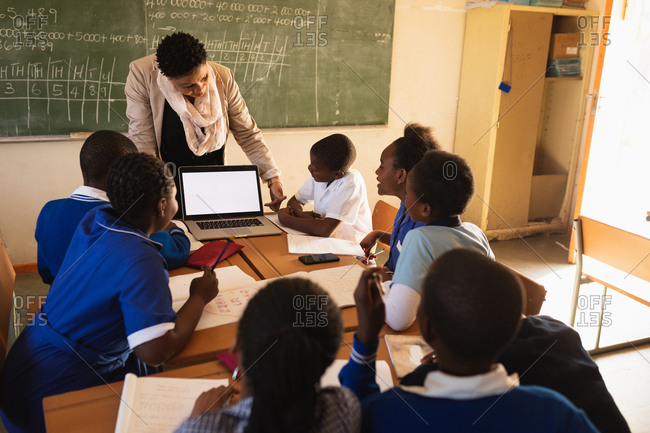 Middle aged African school teacher standing in front of the blackboard showing her pupils a laptop during a lesson in a township elementary school classroom in Cape Town, South Africa