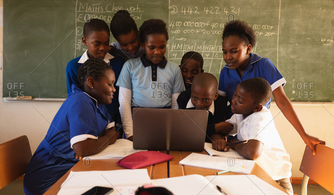 Front view of a group of young African schoolchildren standing and sitting in front of the blackboard gathered around a laptop computer during a lesson in a township elementary school classroom