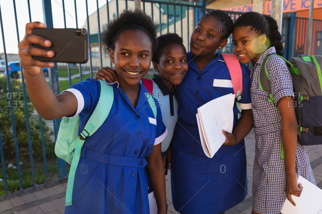 Front view close up of a group of young African schoolgirls having fun posing and taking selfies with a smartphone in a township elementary school playground