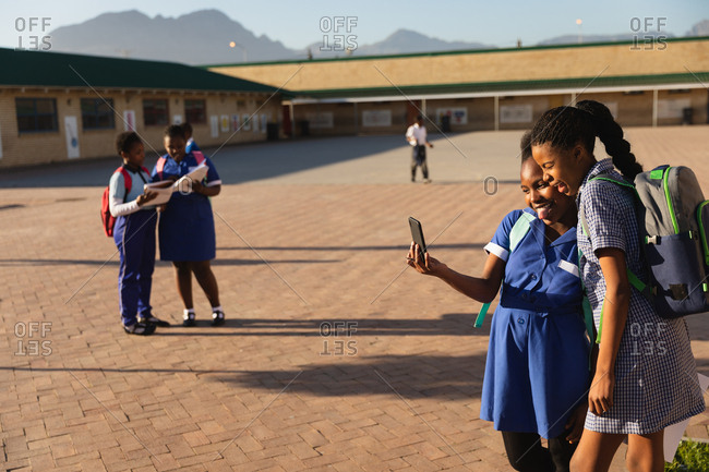 Side view of two young African schoolgirls looking at a smartphone together in a township elementary school playground. In the background two of their classmates are looking at their school books