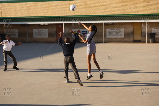 Rear view of a young African schoolgirl and two schoolboys jumping and playing with a ball in the playground at a township elementary school