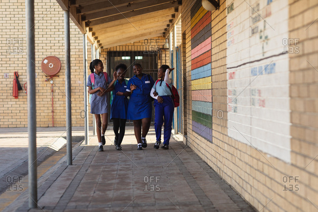Front view of four young African schoolgirls wearing schoolbags smiling and walking with arms linked in the playground of a township elementary school