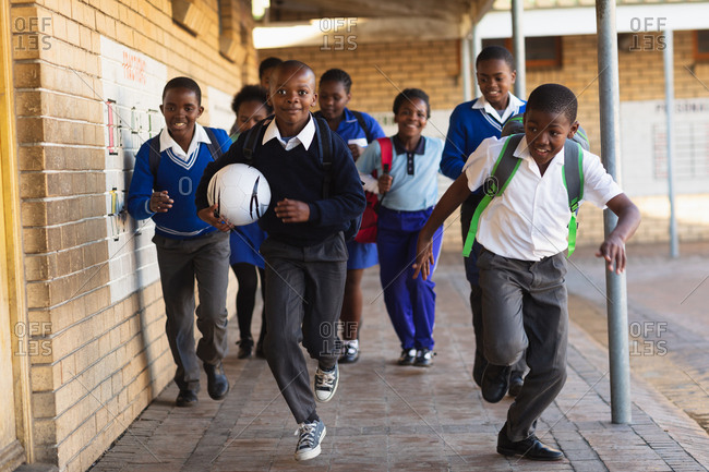 Front view close up of a group of young African schoolchildren running in the school yard with schoolbags and a football at a township elementary school